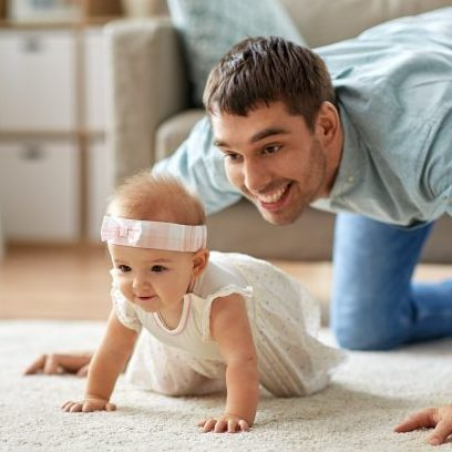 dad watching his baby girl crawl on the carpet and smiling