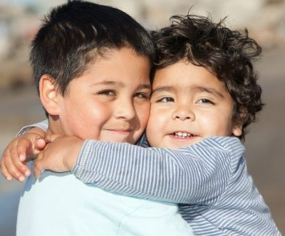 two young brothers embracing; the brother on the left is wearing a white shirt; the brother on the right is wearing a striped shirt