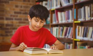 boy wearing a red shirt reading a book in a library