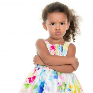 young girl with her arms crossed looks angrily at the camera with her arms crossed